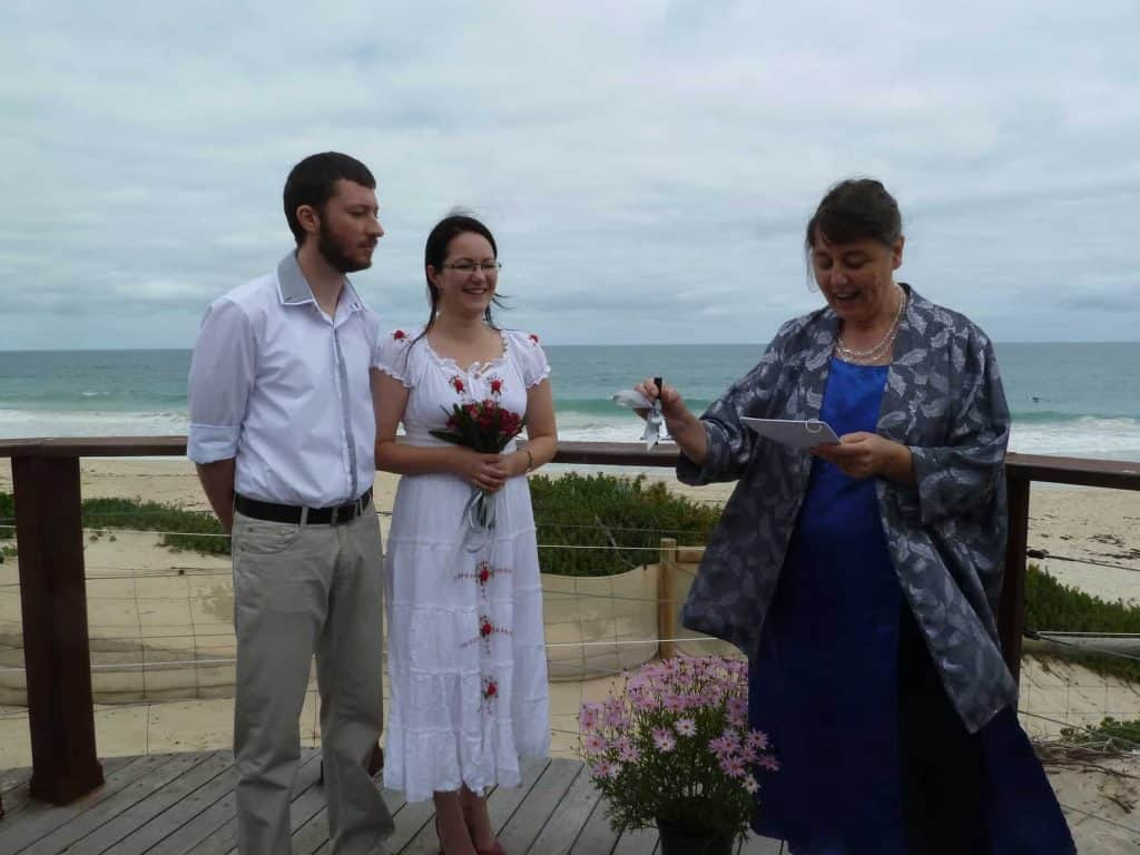 Perth celebrant Ishara rings a bell at a seaside wedding ceremony at City Beach