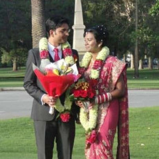 Indian couple with wedding garlands hold marriage certificate in Kings Park, Perth, WA
